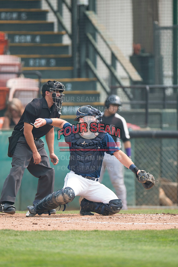 Helena Brewers catcher David Fry (5) throws the ball back to the pitcher in front of home plate umpire John Perez during a Pioneer League game against the Grand Junction Rockies at Kindrick Legion Field on August 19, 2018 in Helena, Montana. The Grand Junction Rockies defeated the Helena Brewers by a score of 6-1. (Zachary Lucy/Four Seam Images)