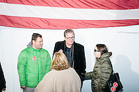 People gather under an American flag after Texas senator and Republican presidential candidate Ted Cruz spoke at a Second Amendment Rally outside Granite State Indoor Range in Hudson, New Hampshire.