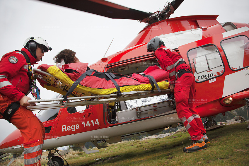 """Switzerland. Canton Ticino. Chironico valley. A Rega Agusta AW109 SP Grand """"Da Vinci"""" helicopter has rescued a swiss german hiker with an injured ankle. The emergency physician, Doctor Michele Musiari L), and the paramedic Paolo Menghetti (R) carries the stretcher by the side door into the helicopter.  All Rega helicopters carry a crew of three: a pilot, an emergency physician, and a paramedic who is also trained to assist the pilot for radio communication, navigation, terrain/object avoidance, and winch operations. The name Rega was created by combining letters from the name """"Swiss Air Rescue Guard"""" as it was written in German (Schweizerische Rettungsflugwacht), French (Garde Aérienne Suisse de Sauvetage), and Italian (Guardia Aerea Svizzera di Soccorso). Rega is a private, non-profit air rescue service that provides emergency medical assistance in Switzerland. Rega mainly assists with mountain rescues, though it will also operate in other terrains when needed, most notably during life-threatening emergencies. As a non-profit foundation, Rega does not receive financial assistance from any government. People in distress can call for a helicopter rescue directly (phone number 1414). The AgustaWestland AW109 is a lightweight, twin-engine, helicopter built by the Italian manufacturer Leonardo S.p.A. (formerly AgustaWestland, Leonardo-Finmeccanica and Finmeccanica). Leonardo S.p.A is an Italian global high-tech company and one of the key players in aerospace. In close collaboration with the manufacturer, the Da Vinci has been specially designed to cater for Rega's particular requirements as regards carrying out operations in the mountains. It optimally fulfills the high demands made of it in terms of flying characteristics, emergency medical equipment and maintenance. Safety, performance and space have been increased, and maintenance and noise emissions reduced. The Chironico valley is a valley lateral to the Levantina valley. 10.09.2017 © 2017 Didier Ruef"""