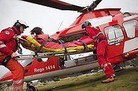 "Switzerland. Canton Ticino. Chironico valley. A Rega Agusta AW109 SP Grand ""Da Vinci"" helicopter has rescued a swiss german hiker with an injured ankle. The emergency physician, Doctor Michele Musiari L), and the paramedic Paolo Menghetti (R) carries the stretcher by the side door into the helicopter.  All Rega helicopters carry a crew of three: a pilot, an emergency physician, and a paramedic who is also trained to assist the pilot for radio communication, navigation, terrain/object avoidance, and winch operations. The name Rega was created by combining letters from the name ""Swiss Air Rescue Guard"" as it was written in German (Schweizerische Rettungsflugwacht), French (Garde Aérienne Suisse de Sauvetage), and Italian (Guardia Aerea Svizzera di Soccorso). Rega is a private, non-profit air rescue service that provides emergency medical assistance in Switzerland. Rega mainly assists with mountain rescues, though it will also operate in other terrains when needed, most notably during life-threatening emergencies. As a non-profit foundation, Rega does not receive financial assistance from any government. People in distress can call for a helicopter rescue directly (phone number 1414). The AgustaWestland AW109 is a lightweight, twin-engine, helicopter built by the Italian manufacturer Leonardo S.p.A. (formerly AgustaWestland, Leonardo-Finmeccanica and Finmeccanica). Leonardo S.p.A is an Italian global high-tech company and one of the key players in aerospace. In close collaboration with the manufacturer, the Da Vinci has been specially designed to cater for Rega's particular requirements as regards carrying out operations in the mountains. It optimally fulfills the high demands made of it in terms of flying characteristics, emergency medical equipment and maintenance. Safety, performance and space have been increased, and maintenance and noise emissions reduced. The Chironico valley is a valley lateral to the Levantina valley. 10.09.2017 © 2017 Didier Ruef"