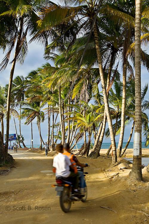 Moto concho (taxi) taking local down the dirt road street along the beach, Las Terranas, Samana, Dominican Republic