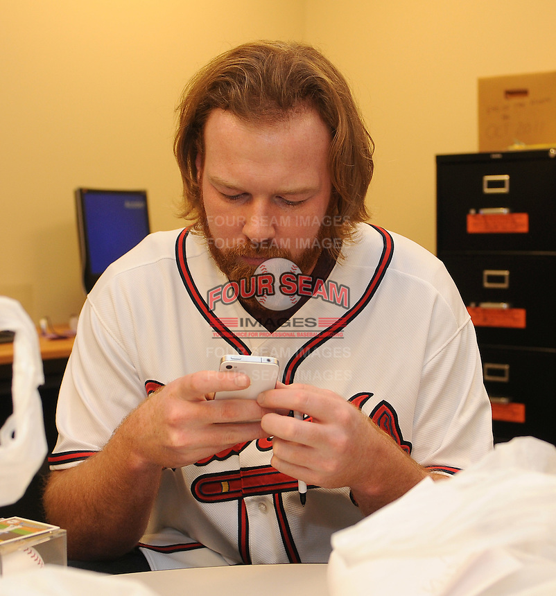 Pitcher Tommy Hanson of the Atlanta Braves checks his iPhone on January 27, 2012 at Academy Sports and Outdoors in Spartanburg, South Carolina. It was the first day of the 2012 Braves Country Caravan, which visits cities all across the South prior to Spring Training. (Tom Priddy/Four Seam Images)