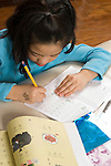 8 year old girl at home doing homework for Chinese language class vertical