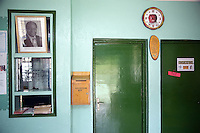 """Kenya. Rift Valley province. Kasambara (20 km from Nakuru). Rhein-Valley hospital is ran by a swiss non-governmental organization (NGO). Reception hall. A picture of the kenyan president Mwai Kibaki. Suggestion box. Blue walls and green doors. Consultation room with a sign saying """" Free"""". A clock with a red apple.  © 2008 Didier Ruef"""