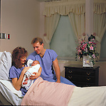 mother, father and newborn infant in delivery room