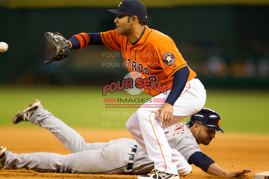 Houston Astros first baseman Carlos Pena (12) catches a pick off attempt as Omar Infante (4) dives back to first during the MLB baseball game against the Detroit Tigers on May 3, 2013 at Minute Maid Park in Houston, Texas. Detroit defeated Houston 4-3. (Andrew Woolley/Four Seam Images).
