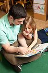 Education Preschool Headstart young male teacher reading to girl