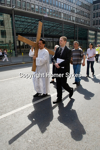 """Easter Good Friday. London UK. Walk of Witness.  """"The Crucifixion on Victoria Street."""" A Christian Cross is carried from the Methodist Central Hall to Westminster Cathedral to Westminster Abbey."""