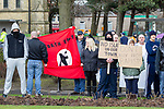 """© Joel Goodman - 07973 332324 . 03/03/2012 . Heywood , UK . Protesters hold up a National Front flag and placards reading """" No Islam in our town """" and """" Don't buy from rapists """" . The National Front hold a rally in protest against an alleged paedophile ring that had been operating in the area . There is currently (3rd March 2012) a case being tried at Liverpool Crown Court in relation to the allegations . Last Thursday (23rd February 2012) a protest organised in the town in relation to the same story resulted in Asian business being attacked by an angry mob . Photo credit : Joel Goodman"""