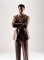 Caucasian looking man wearing a tan suit looking at camera with arms folded