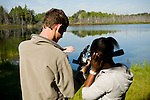 A young man and young woman examine the results of a video recording while filming near a lake in Ontario, Canada. They are part of an international team of students on the Cape Farewell Youth Expedition organized by the British Council of Canada.