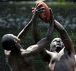 Marcus Banks, left, of New Britain Conn., and Allen Smith of East Hartford, fly out of the water after a football while playing touch football in the pond at Gay City State Park in Hebron Conn., Tuesday, July 6, 2010.  Temperatures reached towards 100 degrees during a heat wave gripping the east coast. (AP Photo/The Journal Inquirer, Jim Michaud)