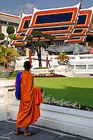 A monk pauses to absorb the beauty at Phra Borom Maha Ratcha Wang, Bangkok.