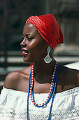 Salvador, Bahia State, Brazil. Beautiful Bahiana woman in a red headscarf wearing beads and large ear rings.