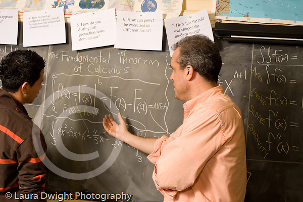 Education High School male math teacher calculus lesson including blackboard working with male student at board horizontal