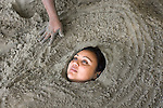 MANUEL ANTONIO, COSTA RICA- JANUARY 11, 2009:  A woman is covered by sand in Espadilla Sur Beach inside Manuel Antonio National Park on January 11, 2009 in Manuel Antonio, Costa Rica.    (Photo by Michael Nagle)
