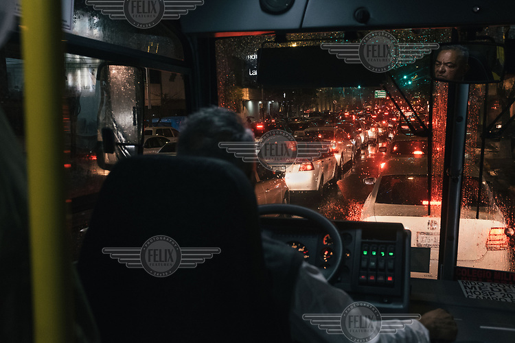 A bus driver stuck in a traffic jam during rush-hour in Mexico City.