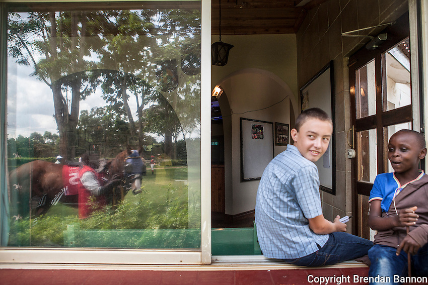 Kids sit on the window of the OBTS (owners, breeders, trainers society) lounge  and watch horses walk through the parade ring before  races at Ngong Racecourse in Nairobi, Kenya. March 17, 2013 Photo: Brendan Bannon