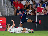 ORLANDO, FL - MARCH 05: Leah Williamson #14 of England slides tackles Crystal Dunn #19 of the United States during a game between England and USWNT at Exploria Stadium on March 05, 2020 in Orlando, Florida.