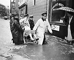 "Mrs. Margaret Garbukas of North Leonard Street is carried to safety the morning of ""Black Friday."" Motor patrolman Joseph Murphy leads the group of rescuers. Fire Battalion Chief John Norton is at the rear."