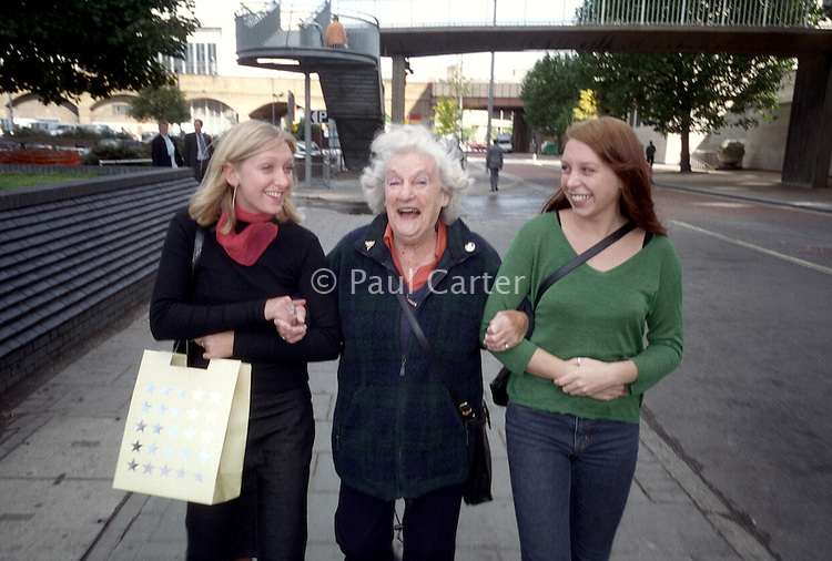 Two sisters and their grandmother walking along a city street, arm in arm.