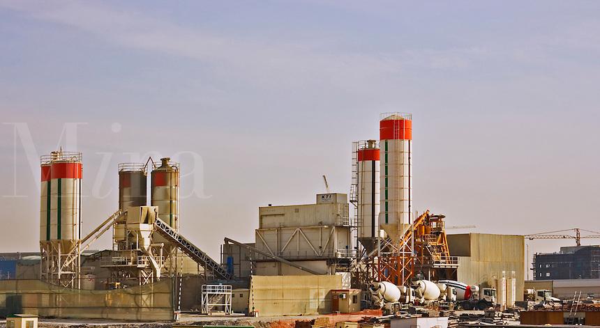 Concrete batching plant loading ready mixed concrete trucks for city construction work.  Dubai. United Arab Emirates.