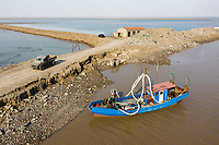A fishing boat near an aquaculture farm next to Bohai Bay, south of the city of Tianjin. As sea levels rise and storm surges increase, this is a continuing struggle for those who rely on farming land in this highly vulnerable region. 2019