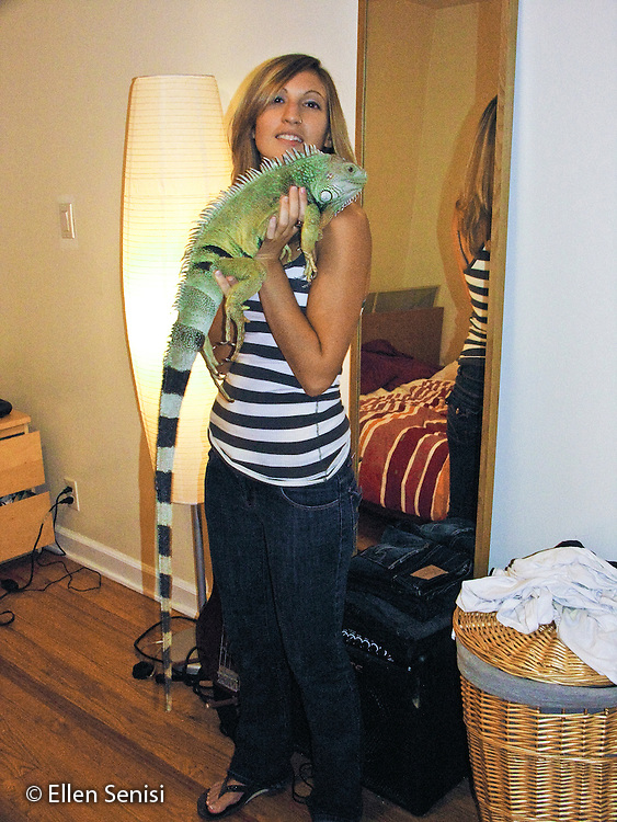 MR / Astoria, New York. Woman (27) holds her pet iguana. Male Green Iguana: Iguana Iguana. (eight years old). One of a series of photographs chronicling the growth and human development of the same person from infancy through to adulthood. MR: Sen1 © Ellen B. Senisi