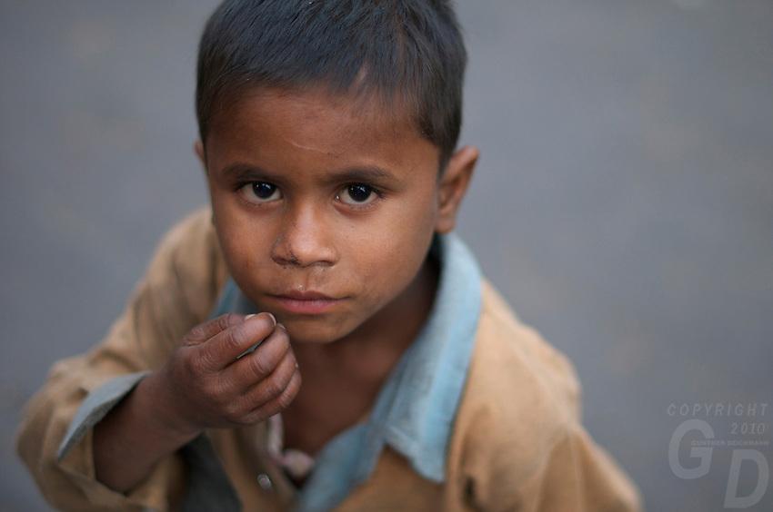 Boy begging in New Delhi India near the Jama Masjid Mosque & Old Delhi