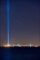 Tribute in Light memorial of 9/11 against Manhattan skyline and Verrazano Bridge. A landing airplane left its light trail behind.