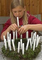 Kinder basteln einen Lichterkranz für die Adventszeit, Adventskranz, Kind steckt Kerze mit Draht in den Kranz, Lichterkranz mit 24 brennenden Kerzen für den 1. bis 24. Dezember