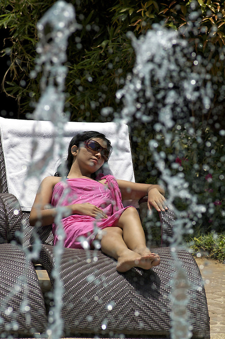 Girl relaxing at the pool side, with a fountain BORACAY ISLAND PHILIPPINES
