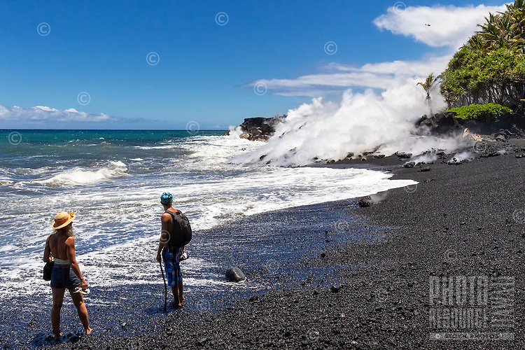 A couple observes lava flowing into the ocean at Fox's Landing black sand beach on the Big Island; a helicopter hovers in the distance.