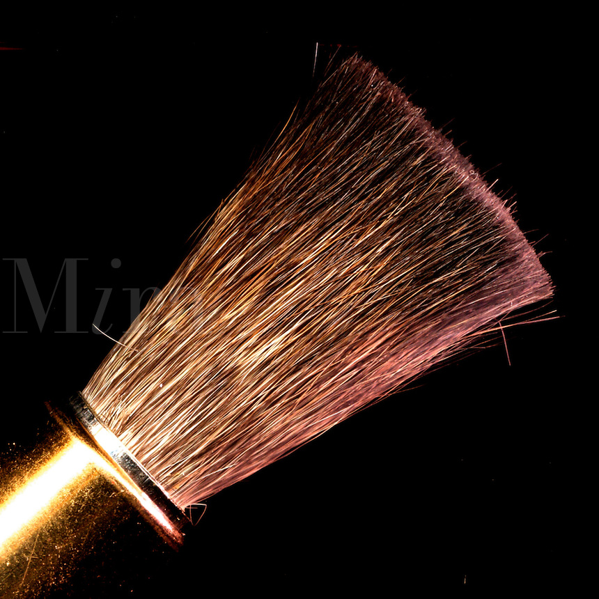 Closeup of a camel hair makeup brush in a brass sleeve.
