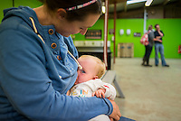 """A mother breastfeeding her baby of eight months in a barn at a visitor farm park.<br /> <br /> Image from the breastfeeding collection of the """"We Do It In Public"""" documentary photography picture library project: <br />  www.breastfeedinginpublic.co.uk<br /> <br /> <br /> Gloucestershire, England, UK<br /> 30/09/2013<br /> <br /> © Paul Carter / wdiip.co.uk"""