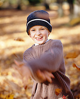 A boy throwing autumn leaves