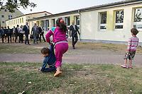 Zentrale Auslaenderbehoerde und BAMF-Aussenstelle in Eisenhuettenstadt.<br /> Bundesinnenminister Thomas de Maiziere und brandeburgs Ministerpraesident Dietmar Woidke besuchten am Donnerstag den 13. August 2015 die Zentrale Auslaenderbehoerde und BAMF-Aussenstelle in Eisenhuettenstadt. Sie liessen sich von Mitarbeitern die Situation in der Einrichtung zeigen und erklaeren, sprachen mit Fluechtlingen und besichtigten das auf dem Gelaende befindliche Abschiebegefaengnis.<br /> Der Besuch des Bundesinnenministers und des Ministerpraesidenten wurde von etwa 40 Journalisten begleitet.<br /> Im Bild: Fluechtlingskinder vor einem der Verwaltungsgebaeude. Im Hintergrund der Innenminister, der Ministerpraesident und der Pressetross.<br /> 13.8.2015, Eisenhuettenstadt/Brandenburg<br /> Copyright: Christian-Ditsch.de<br /> [Inhaltsveraendernde Manipulation des Fotos nur nach ausdruecklicher Genehmigung des Fotografen. Vereinbarungen ueber Abtretung von Persoenlichkeitsrechten/Model Release der abgebildeten Person/Personen liegen nicht vor. NO MODEL RELEASE! Nur fuer Redaktionelle Zwecke. Don't publish without copyright Christian-Ditsch.de, Veroeffentlichung nur mit Fotografennennung, sowie gegen Honorar, MwSt. und Beleg. Konto: I N G - D i B a, IBAN DE58500105175400192269, BIC INGDDEFFXXX, Kontakt: post@christian-ditsch.de<br /> Bei der Bearbeitung der Dateiinformationen darf die Urheberkennzeichnung in den EXIF- und  IPTC-Daten nicht entfernt werden, diese sind in digitalen Medien nach §95c UrhG rechtlich geschuetzt. Der Urhebervermerk wird gemaess §13 UrhG verlangt.]