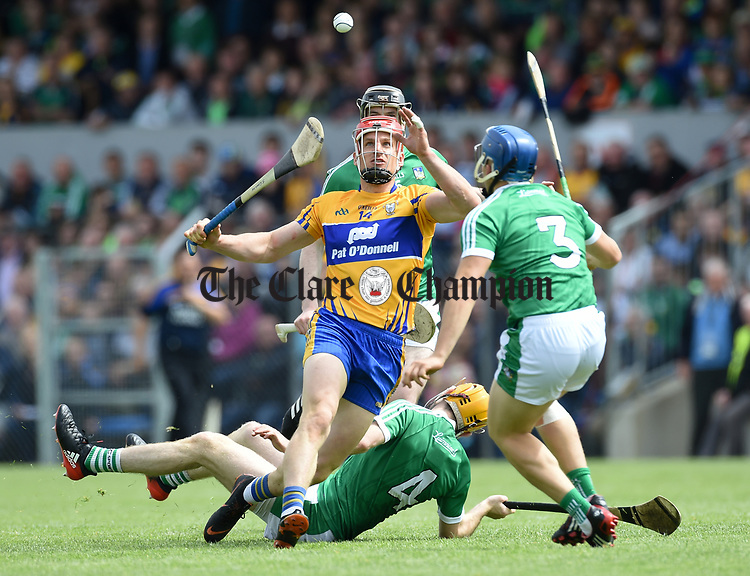 John Conlon of Clare in action against Ritchie English, Declan Hannon and Mike Casey of Limerick during their Munster championship game in Ennis. Photograph by John Kelly.