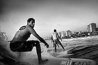 Surfers ride a wave in the Mediterranean Sea off the shore of Gaza City.