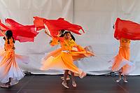 Girls wearing beautiful orange dresses dancing Chinese Red Fan Dance, Northwest Folklife Festival 2016, Seattle Center, Washington, USA.