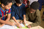 Public elementary school for gifted children grades K-6: Science lab three students measuring range of motion, filling out data sheets Grade 5