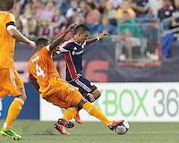 Houston Dynamo defender Jermaine Taylor (4) thwarts New England Revolution midfielder Diego Fagundez (14). In a Major League Soccer (MLS) match, Houston Dynamo (orange) defeated the New England Revolution (blue), 2-1, at Gillette Stadium on July 13, 2013.