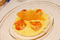 A creamy risotto with confit lemon and thyme grilled scampis on a glass plate with a parmesan cracker on a white table cloth, Restaurant Les Berceaux, Patrick Michelon, Epernay, Champagne, Marne, Ardennes, France, low light grainy grain