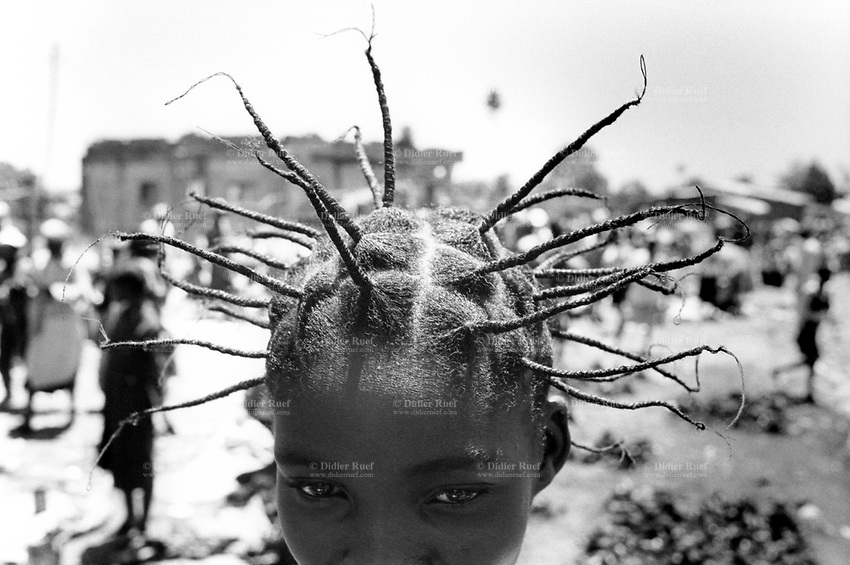 Angola. Province of Bié. Kuito. A young girl in the market with a typical african hair style. © 2000 Didier Ruef
