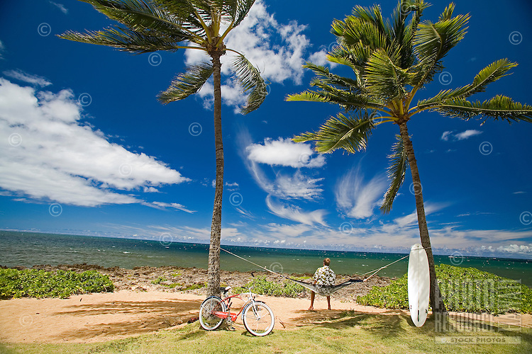 Young man relaxing in a hammock in Haleiwa Park  by the sea, bike and surfboard ready