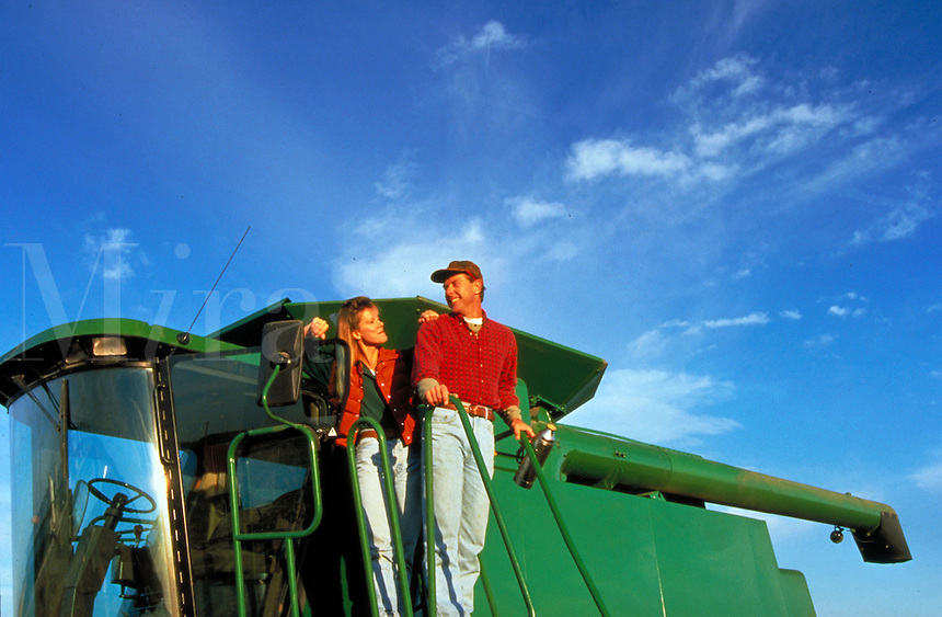 Farm couple on combine during autumn corn and soybean harvest in the midwest.