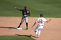 Pittsburgh Pirates second baseman Rodolfo Castro (64) throws to first base as Chris Shaw (26) slides in during a Major League Spring Training game against the Baltimore Orioles on February 28, 2021 at Ed Smith Stadium in Sarasota, Florida.  (Mike Janes/Four Seam Images)