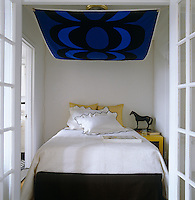 The tiny bedroom just fits a small double bed which has a graphic deep blue fabric hanging over it