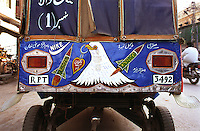 "© Piers Benatar/Panos Pictures..Rawalpindi, Pakistan. 2001...Pakistan is very proud of its status as the only Muslim nuclear power, a pride which manifests itself in sculptures, murals and merchandising paraphernalia depicting its Ghauri and Shaheen missiles. Here, an auto-rickshaw is decorated with Nike logos and missiles. The inscription reads ""Long Live Pakistan""."