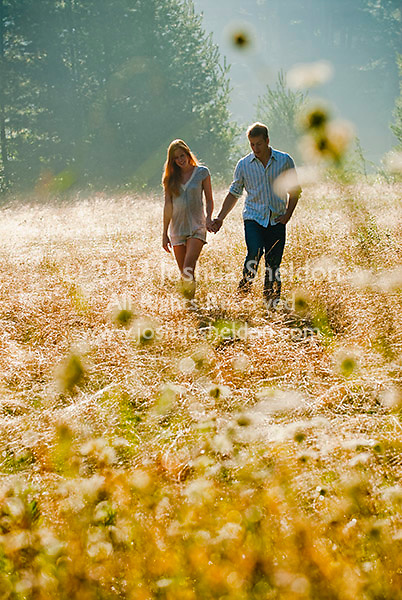 Young couple walking through field holding hands